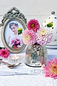 Mercury glass vase and pink dahlias on lace doily and photo of girl in antique picture frame