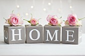 Pastel pink roses on card cubes with decorative letters spelling 'HOME'