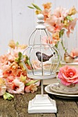 White birdcage ornament, roses and salmon-pink gladioli