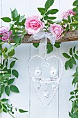 Heart-shaped, ornate metal welcome sign hanging from branch decorated with garland of roses