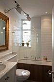 Modern, white-tiled bathroom with traditional ambiance; bathtub with rainfall shower behind glass screen, Tolomeo wall lamps and gilt-framed mirror