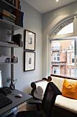 Antike gepolsterte helle Sitzbank vor Rundbogenfenster, seitlich moderner Arbeitstisch im Metallregal integriert