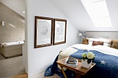 Double bed below skylight and view into bathroom with light beige tiles through open doorway