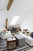 White armchair and sofa around cube table and pouffe in attic room