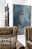 Wing-back armchairs with striped pale brown upholstery in front of modern artwork