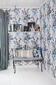 Filigrane Metallbank mit Sitzpolster und Kissen in romantisch tapezierter Zimmerecke mit blauem Blumenmuster