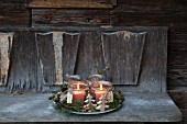 with two lit candles in mason jars on weathered wooden bench
