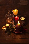 Dim light from lit candles and tealights of festive arrangement