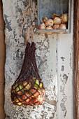 Makramee-Einkaufsnetz mit geernteten Äpfeln an Fleischerhaken