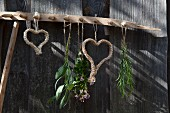 Macrame hearts hung on vintage wooden rake against weathered board wall