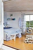 View from terrace into maritime-style bedroom in shades of blue