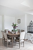 Wooden dining table, antique upholstered chairs and vintage birdcage on tray table in dining room