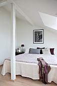 Double bed with bedspread in corner of room under sloping ceiling