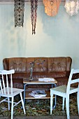 Simple kitchen chairs and leather couch around delicate retro tea trolley