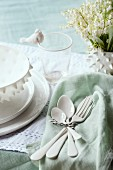 White ceramic cutlery on pastel green napkin next to place setting