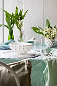 White place setting, lily of the valley and pastel green tablecloth on table outdoors