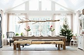 Branch suspended above festively set dining table an Christmas tree in background