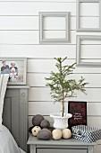 Nadelbäumchen in Amphore, Filzkugeln und Weihnachtskarte auf Nachttisch neben Bett