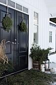 Advent arrangement of fir branches on veranda of Scandinavian house