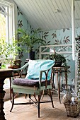 Wicker armchair in vintage-style attic room with potted plants on plant stands against leaf-patterned wallpaper