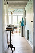 Vintage-style tall bistro table in bedroom; tailors' dummy in background