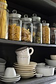White crockery and storage jars in open-fronted, wall-mounted cabinet