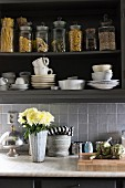 Vase of flowers on kitchen counter below white crockery and storage jars in open-fronted wall cabinets