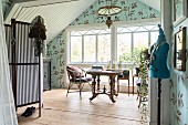 Vintage-style room with gable.end wall, tailors' dummy, antique table below lattice window and leaf-patterned wallpaper