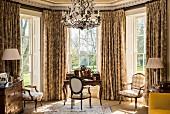 Klassischer Schreibtisch mit barocken Stühlen in einem Erker mit Sprossenfenstern und üppigen Vorhängen