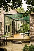 Modern angebauter Wintergarten an ein englisches Landhaus aus Stein