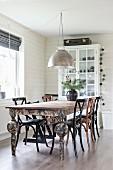 Holzstühle um Esstisch mit abblätternder Farbe, unter Pendelleuchte mit Metallschirm, in Essbereich mit weisser Holzverkleidung