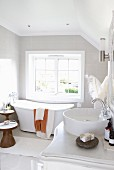 Round countertop basin on white-painted chest of drawers in front of free-standing, modern bathtub and lattice window in modern bathroom iith vintage ambiance