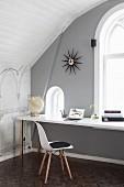 Klassikerstuhl mit weisser Sitzschale vor Arbeitstisch am Fenster, grau getönte Wand, im Dachzimmer mit Tonnendecke