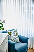 Scatter cushion with large-format floral pattern on light blue armchair in front of white, floor-length curtains on window