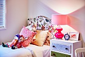 Stofftiere und Kissen auf Bett mit Kopfteil und Blumenmuster auf Stoffbezug, daneben Tischleuchte in Rosa auf Nachttisch
