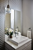 Washstand with base cabinet below mirror on wall with grey, retro pattern
