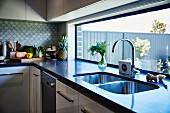 Twin sink in dark counter below long ribbon window in modern fitted kitchen
