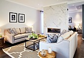 Elegant sofa set with pale covers and modern coffee table on rug with large ornamental pattern in open-plan interior with fireplace in partition wall