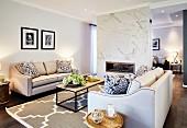Elegante Sofagarnitur mit hellem Bezug und moderner Couchtisch auf Teppich, mit grossformatigem Ornament Muster in offenem Wohnraum, Kamin in Raumteiler