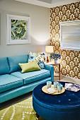Tablett mit Tassen auf rundem Polstertisch mit blauem Satinbezug und hellblaues Sofa in Wohnzimmer, seitlich tapezierte Wand mit Retro Ornament Muster