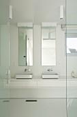 Offene Glastür und Blick auf moderne Waschtischzeile in Weiss mit zwei Becken, vor schmalen, vertikalen Wandspiegeln