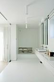 Minimalistische Waschtischzeile mit weißem Unterschrank, eingespannt zwischen Wänden, in weißem Badezimmer