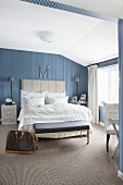 Elegant, vintage-style bedroom with blue and white striped wallpaper