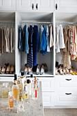 Verschiedene Parfumflakons vor offenem Kleiderschrank mit Damenschuhen und Damenkleidung