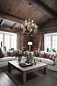 Solid wooden coffee table and pale sofa set under light fitting made from antlers in living area of wooden house