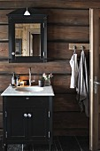 Washstand with base cabinet against board wall