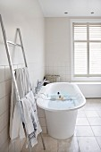 Free-standing bathtub with bath caddy and stainless steel ladder-style towel rail in modern bathroom