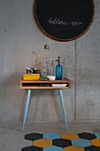 Vintage bottles on console table with legs painted pale blue against exposed concrete wall