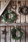 Various wreaths of for branches on rustic wooden wall