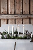 Four white candles in DIY candelabra made from half a birch log on wooden tray